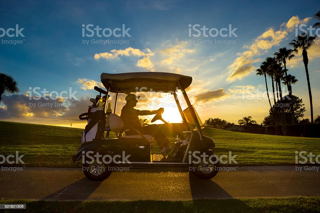 Senior golfer driving golf cart stock photo