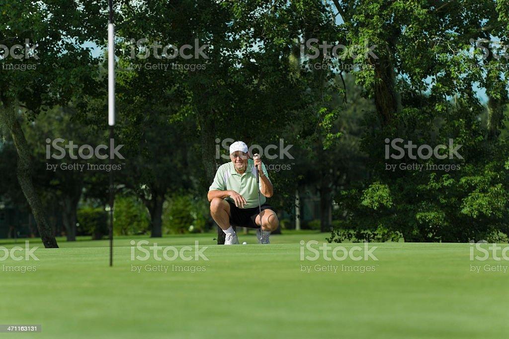 Senior golfer preparing to put royalty-free stock photo