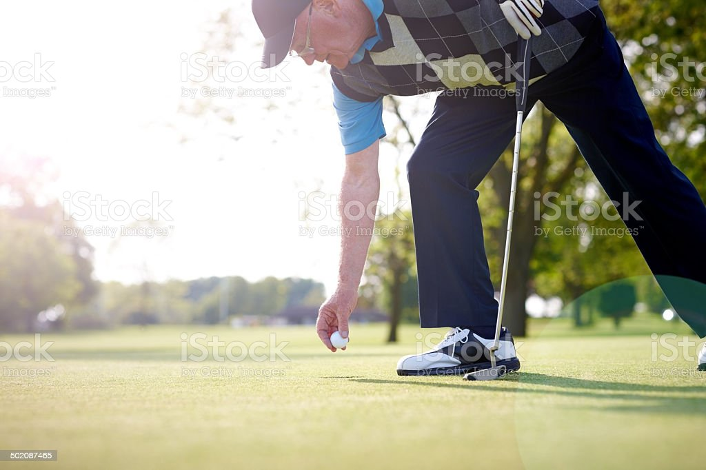 Senior golfer taking ball out of the hole stock photo