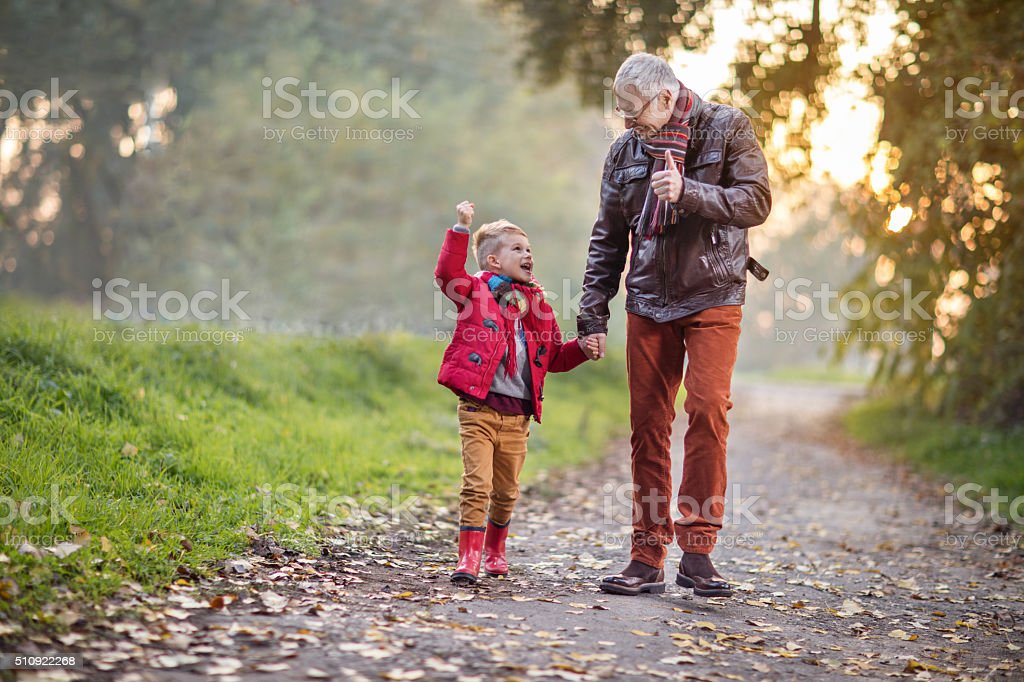 Senior grandfather walking with his grandson and talking to him. stock photo
