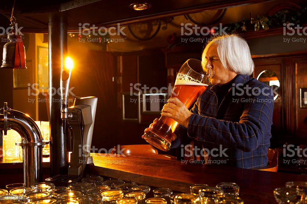 Senior gray-haired man drinking  huge glass of beer in pub stock photo
