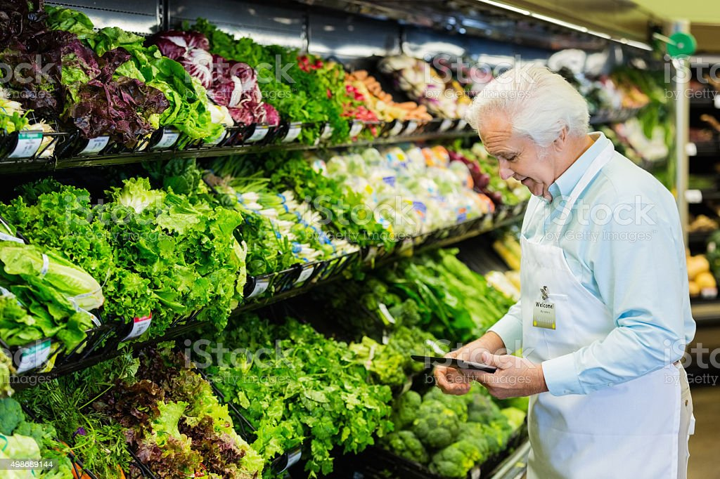 Senior grocery store manager taking inventory with digital tablet stock photo