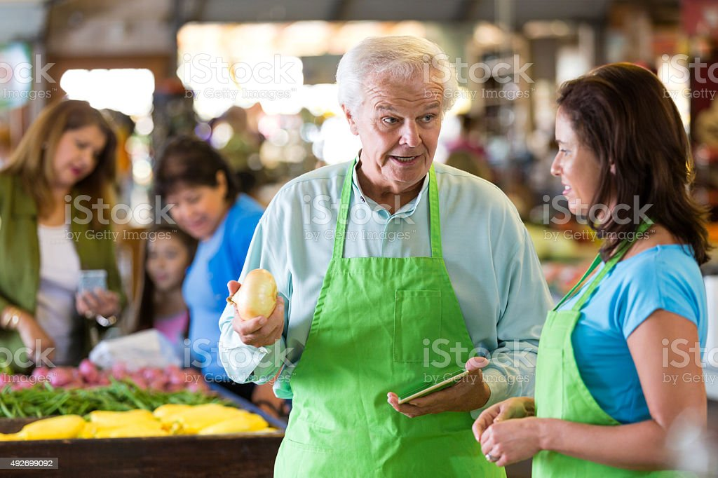 Senior grocery store owner training employee in produce section stock photo