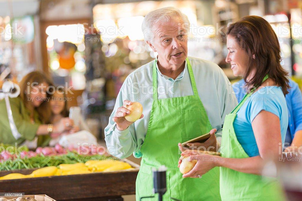 Senior grocery store owner training new employee stock photo