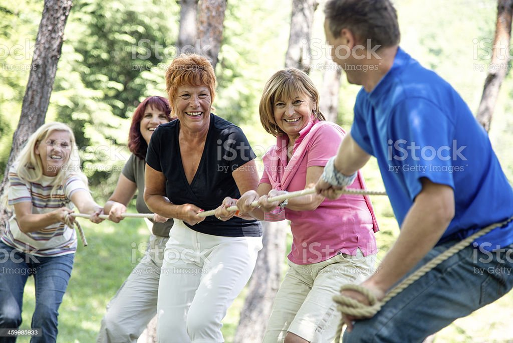 A senior group of people playing tug of war royalty-free stock photo