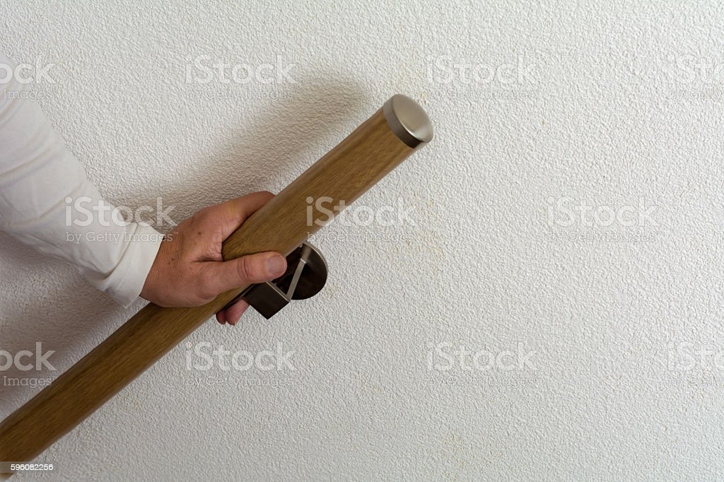 senior hand holding handrail going up stock photo
