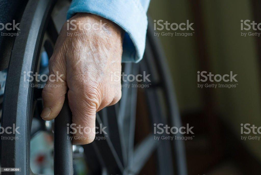 Senior hand on wheelchair wheel stock photo