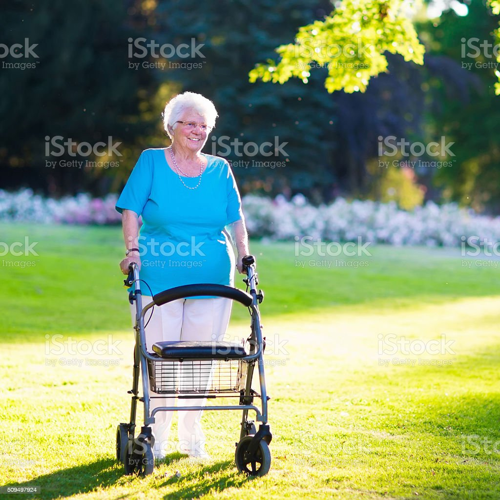 Senior handicapped lady with a walker in a park stock photo