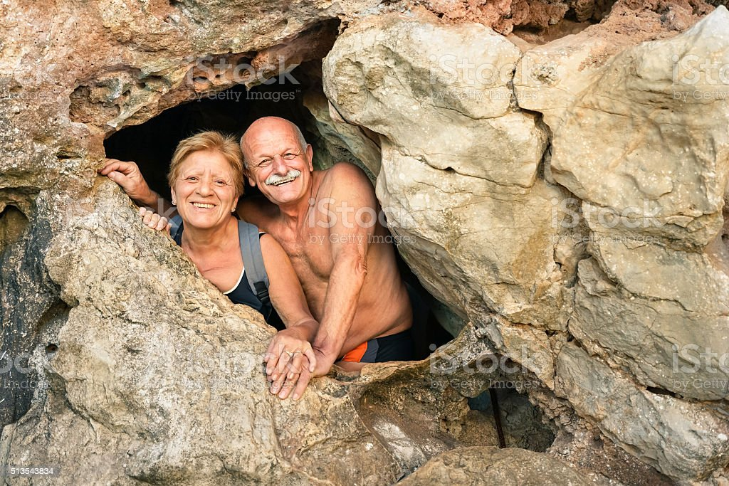 Senior happy couple having fun at cave entrance in Coron stock photo