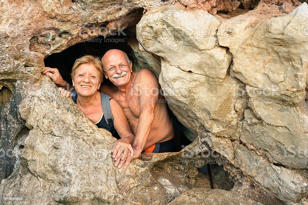 Senior happy couple having fun at cave entrance in Coron stock photo