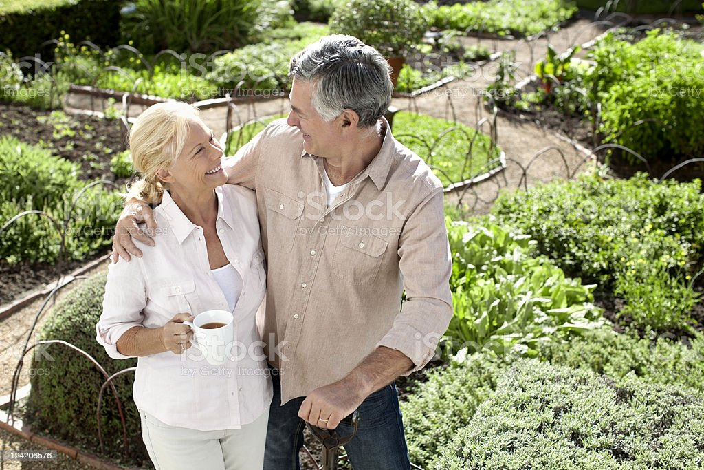 Senior happy couple looking at each other holding teacup in domestic garden royalty-free stock photo