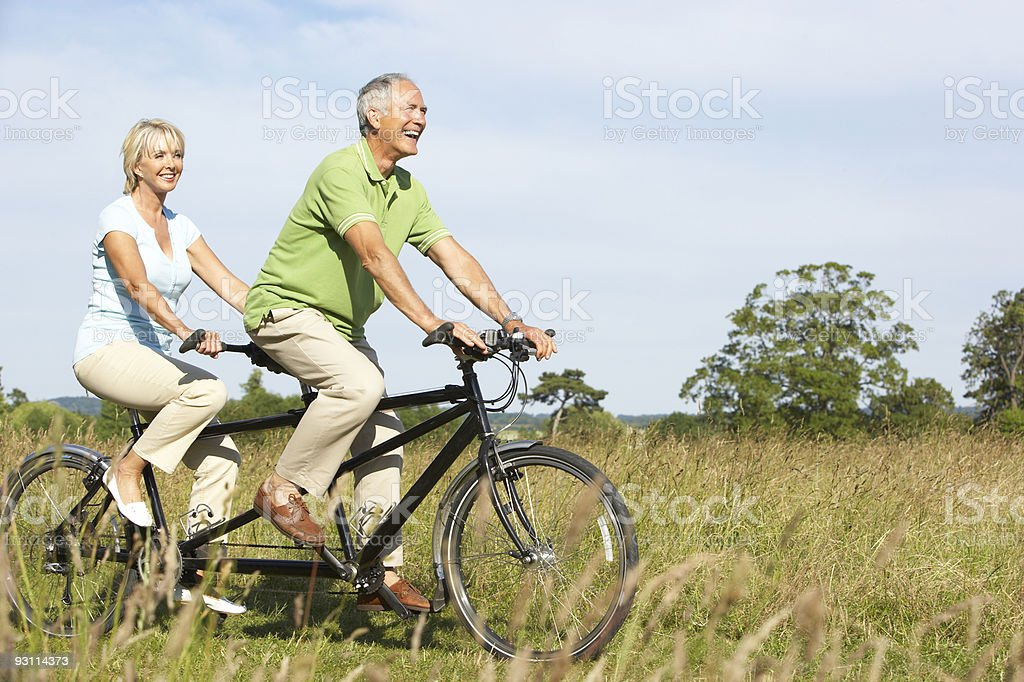 Senior happy couple riding a bike in a grass field stock photo