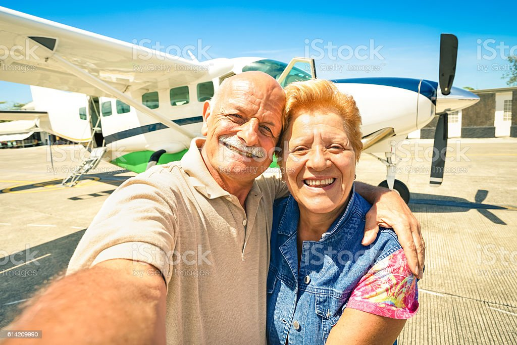 Senior happy couple taking selfie with private ultralight plane travel stock photo