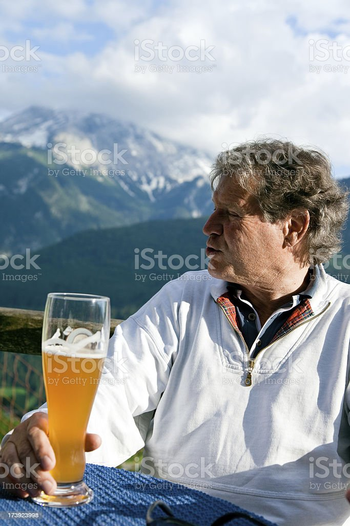 senior having a drink in an alpine restaurant royalty-free stock photo