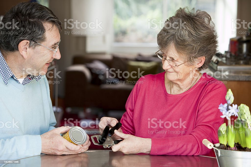 senior having occupational therapy home assessment holding can opener stock photo