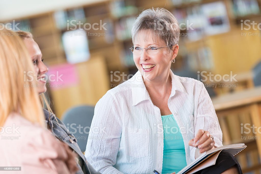 Senior high school teacher having conferenct with student and parent stock photo