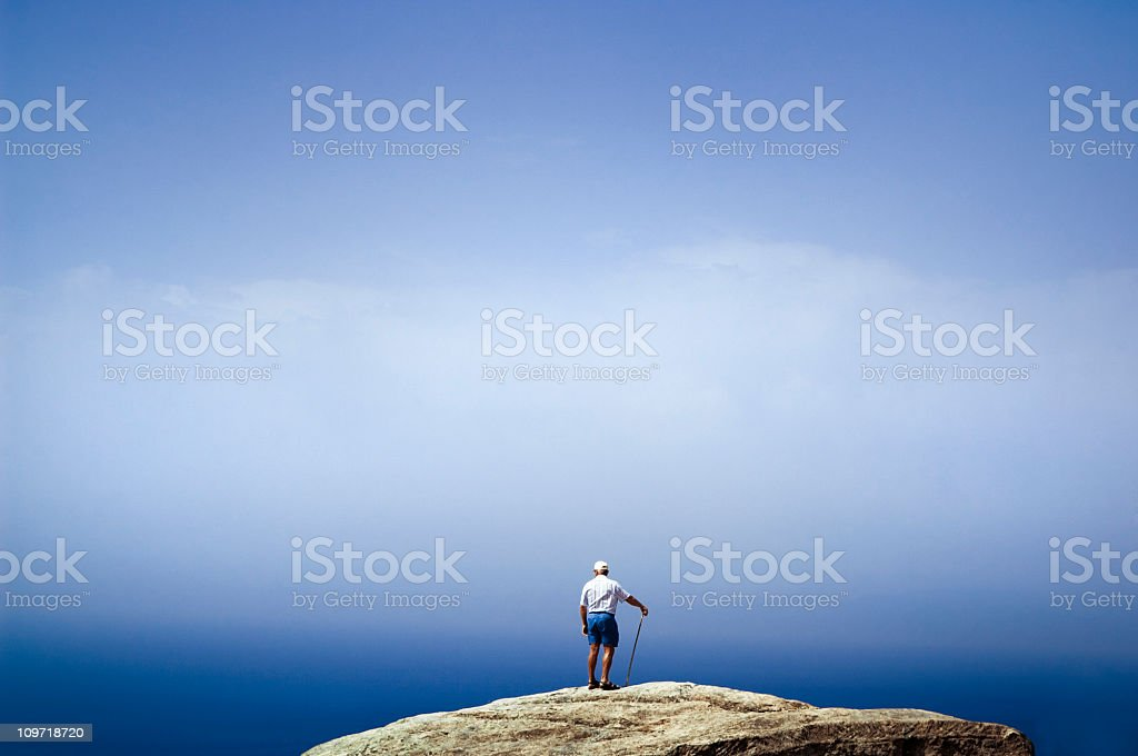 Senior Hiker Standing on Mountain Overlooking Sky royalty-free stock photo