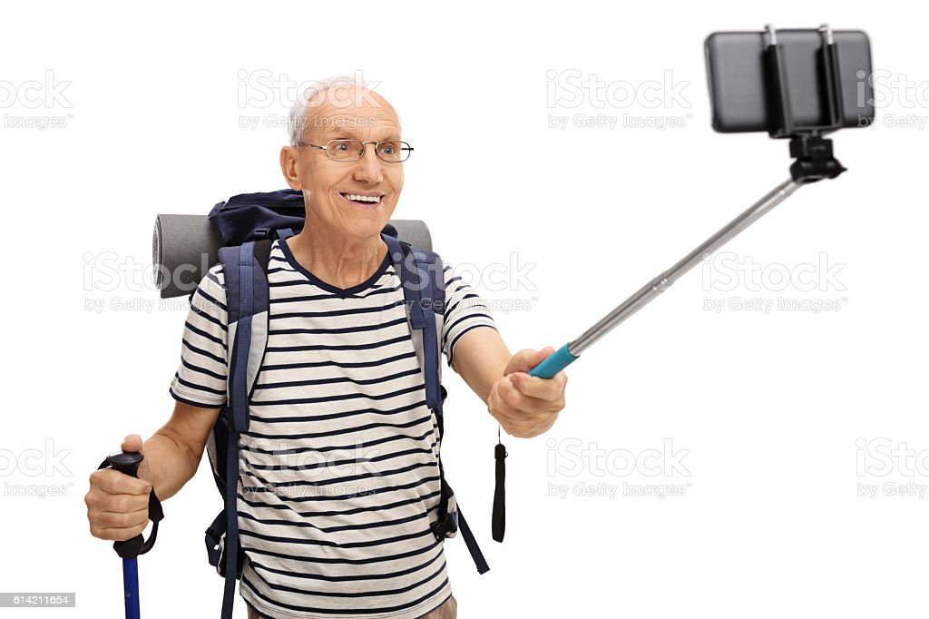Senior hiker taking a selfie with a stick stock photo