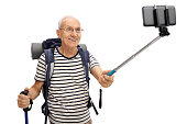 Senior hiker taking a selfie with a stick