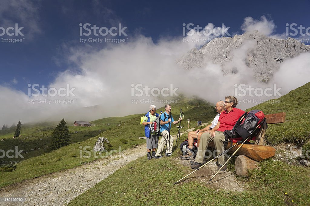 senior hikers at short break on bench in beautiful mountains royalty-free stock photo