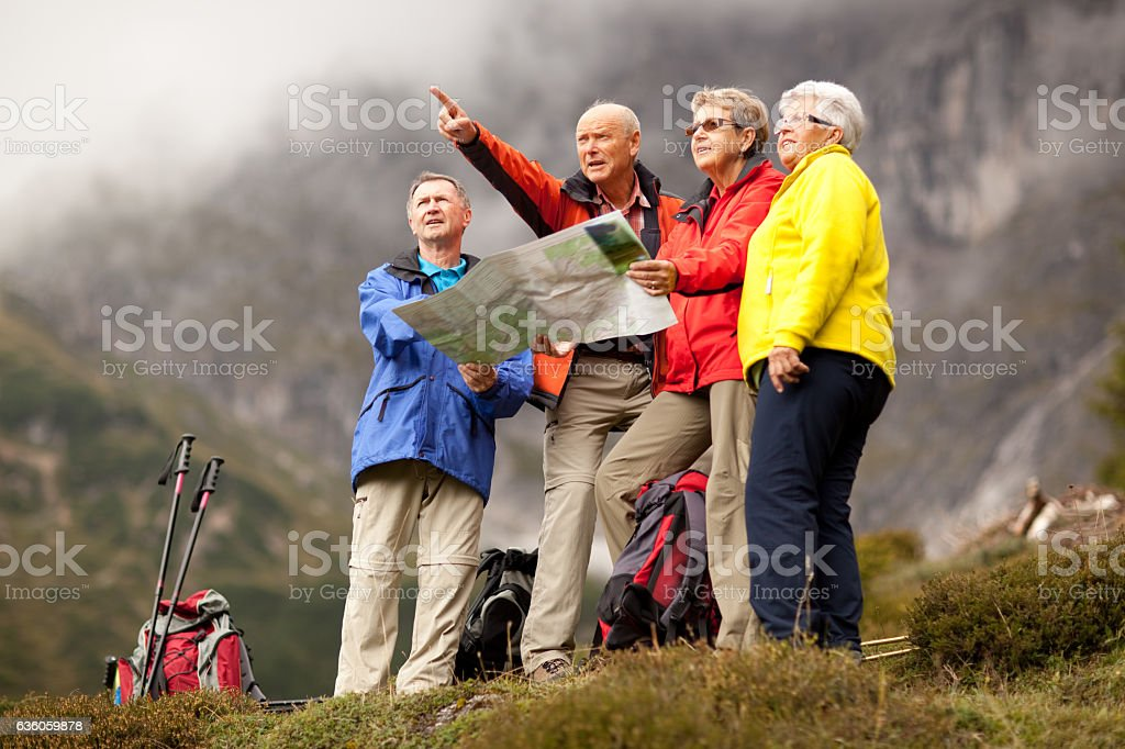 senior hikers choosing right trail with map stock photo
