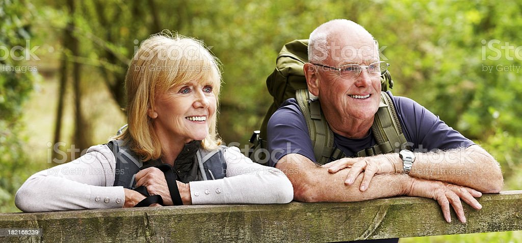 Senior hikers standing by a fence royalty-free stock photo
