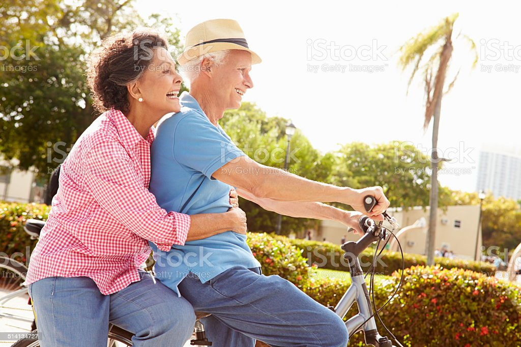 Senior Hispanic Couple Riding Bikes In Park stock photo