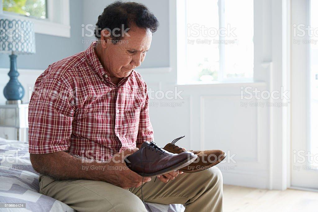 Senior Hispanic Man Suffering With Dementia Trying To Dress stock photo