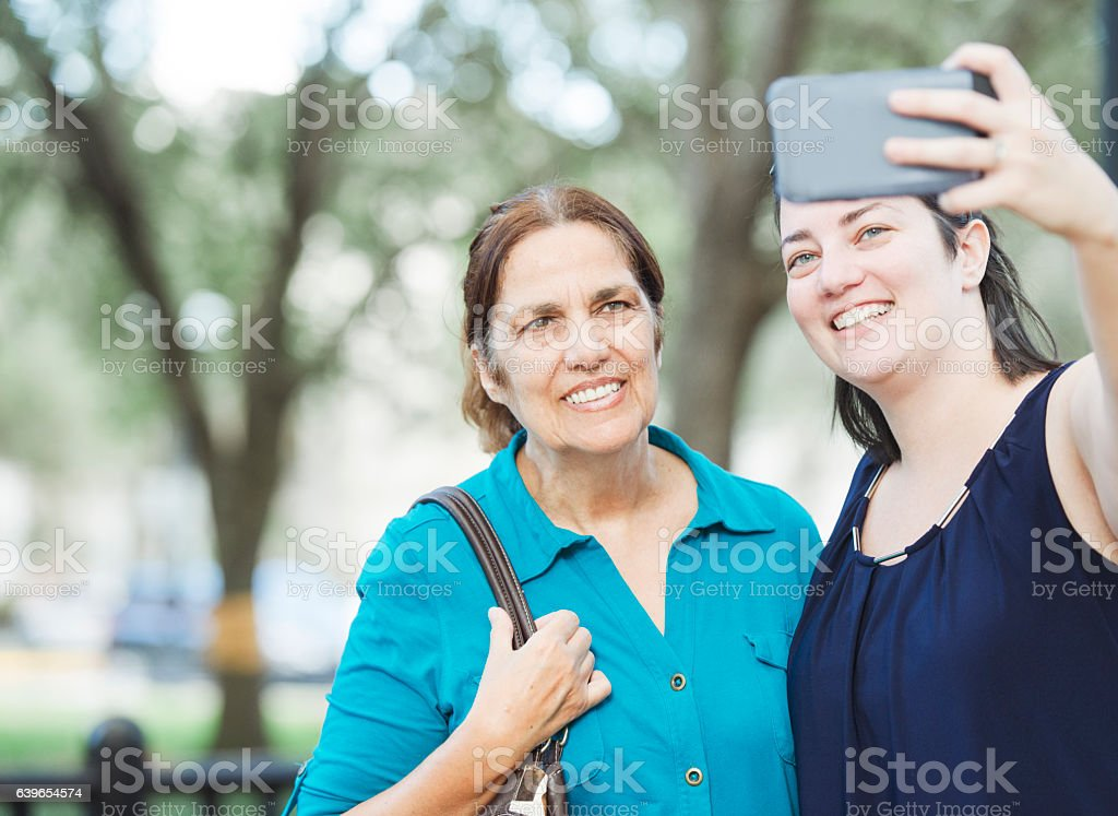 Senior Hispanic Mother and Caucasian Daughter Taking Selife Orlando Florida stock photo