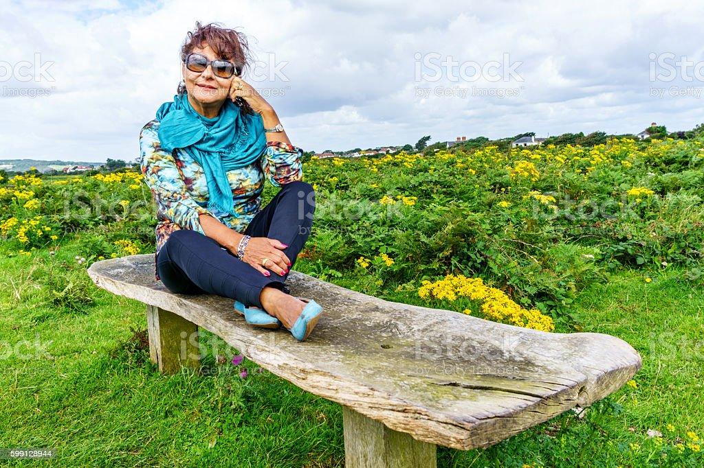 Senior hispanic woman sitting on remote coastal headland stock photo