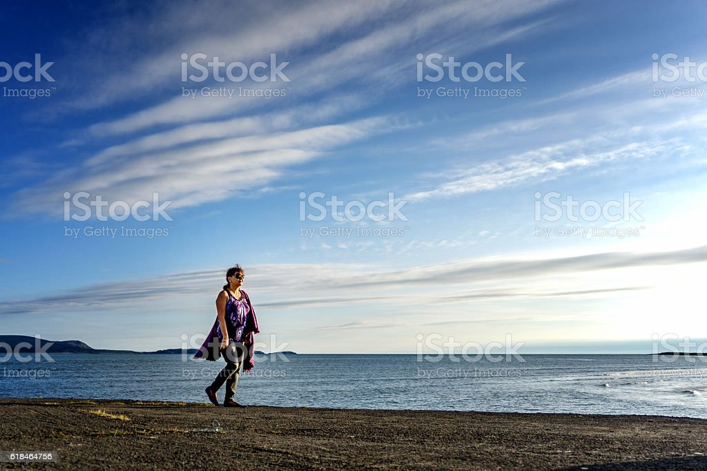 Senior hispanic woman walking on coastal headland stock photo