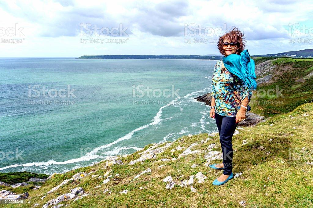 Senior hispanic woman walking on remote coastal headland stock photo