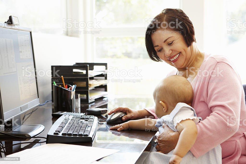Senior Hispanic woman with computer and baby royalty-free stock photo