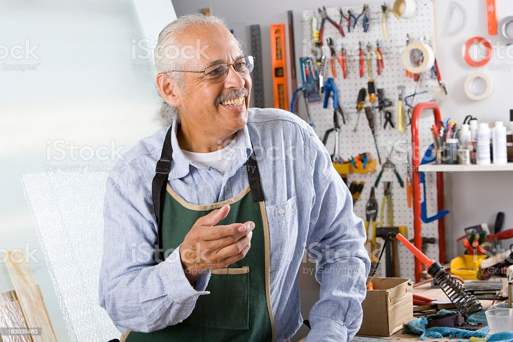 Senior Hispanic worker with tools in repair shop stock photo