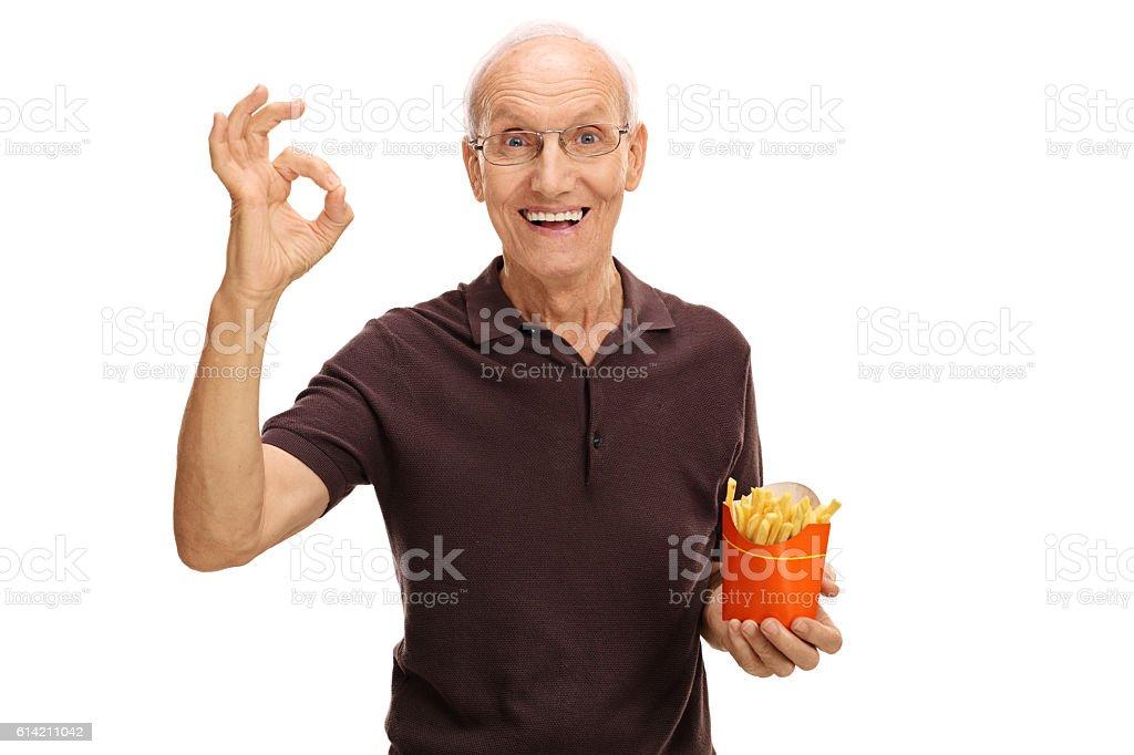 Senior holding bag of fries and making ok sign stock photo