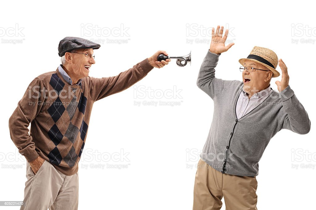 Senior honking a horn and scaring another senior stock photo