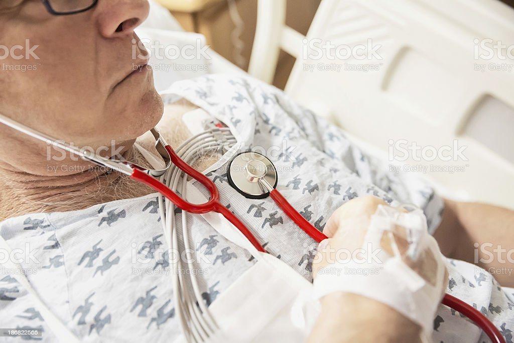 Senior hospital patient uses stethoscope and listens to heart royalty-free stock photo