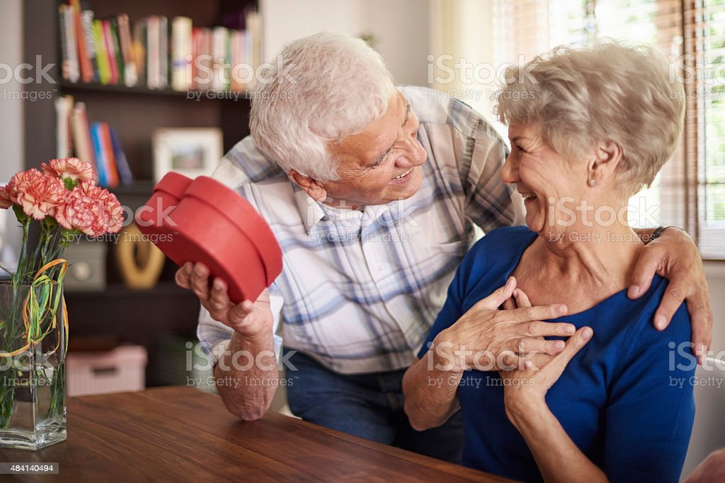 Senior husband giving a present to his wife stock photo