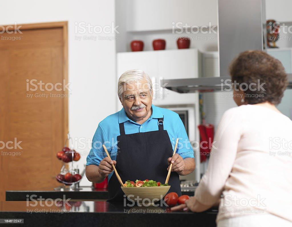 Senior husband preparing a salad in the kitchen royalty-free stock photo