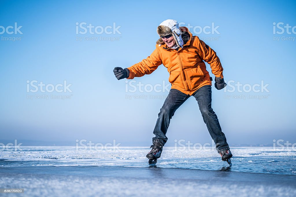 senior ice skater on frozen lake showing his skills stock photo