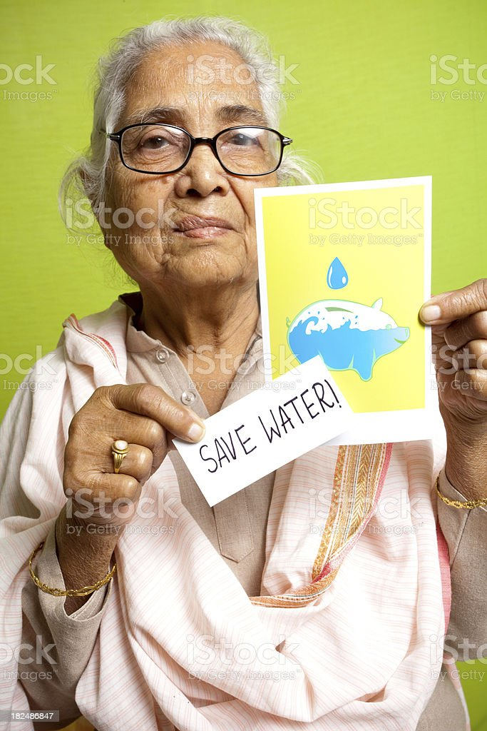 Senior Indian female showing Save Water message poster leaflet royalty-free stock photo