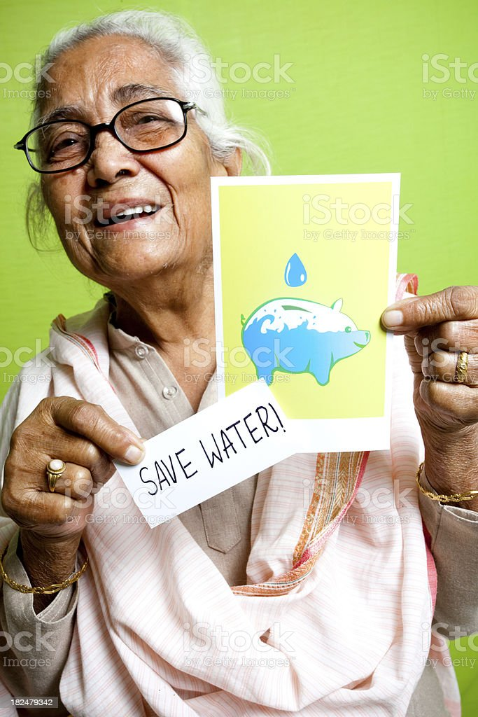 Senior Indian lady showing Save Water sign message poster leaflet stock photo