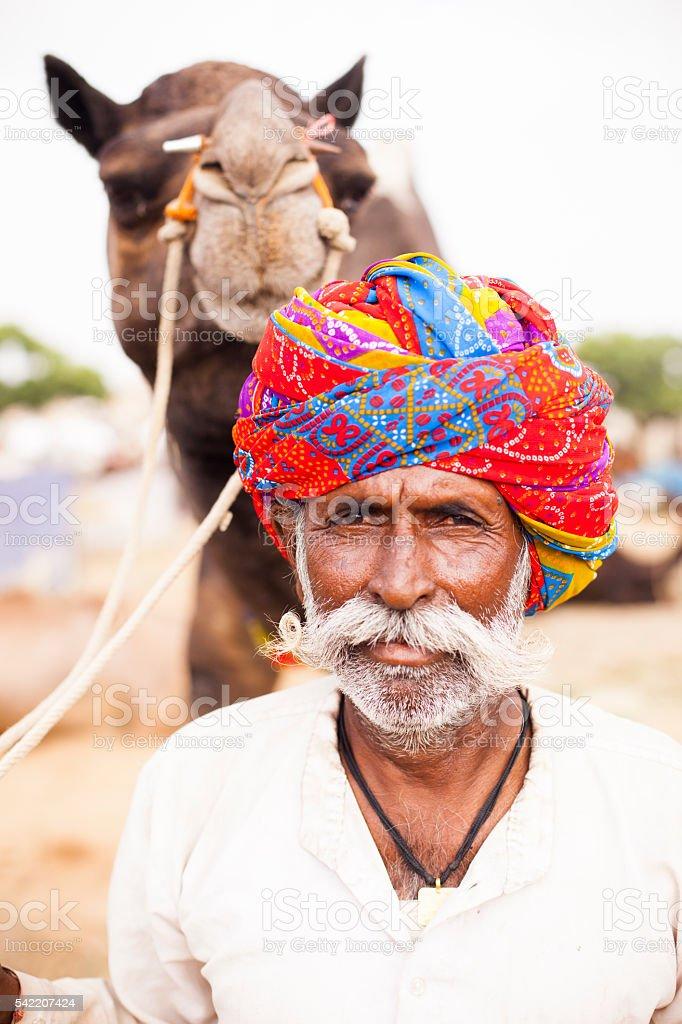 Senior Indian Man with Camel at Pushkar Camel Fair stock photo