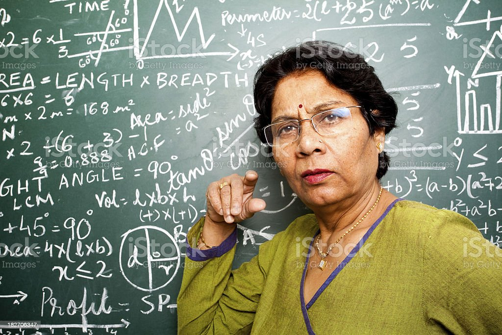 Senior Indian Mathematics Teacher in a Classroom royalty-free stock photo