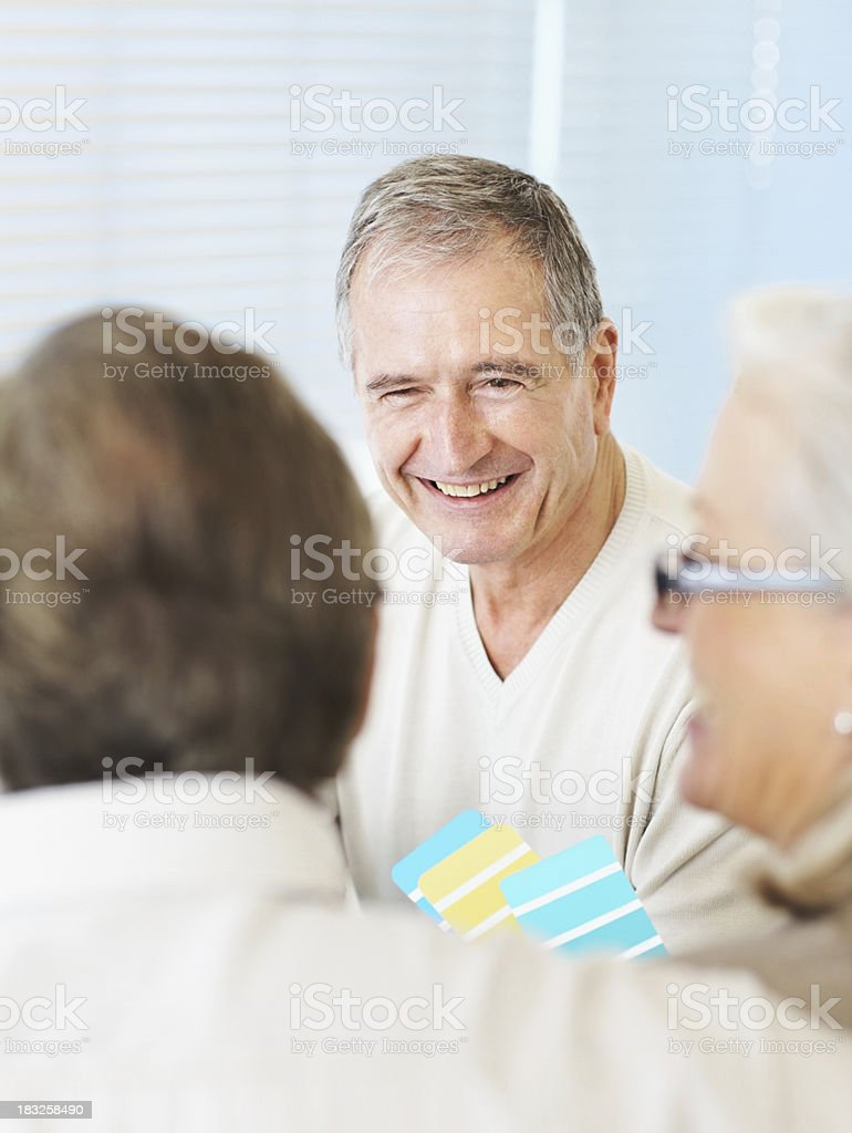 Senior interior designer assisting couple with color swatches royalty-free stock photo