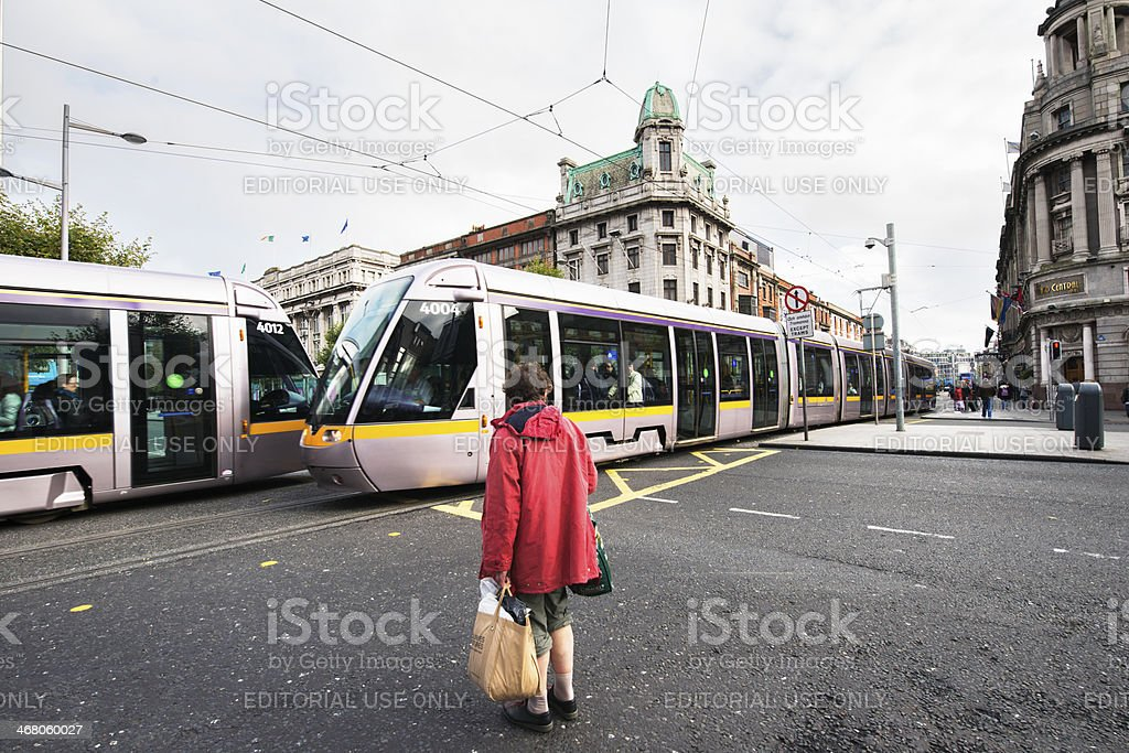 Senior Irish Woman Waiting for Trams Crossing Street Dublin Ireland royalty-free stock photo