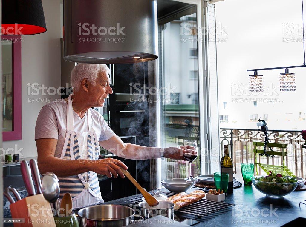 senior Italian man cooks meal drinks wine  stylish modern apartment stock photo