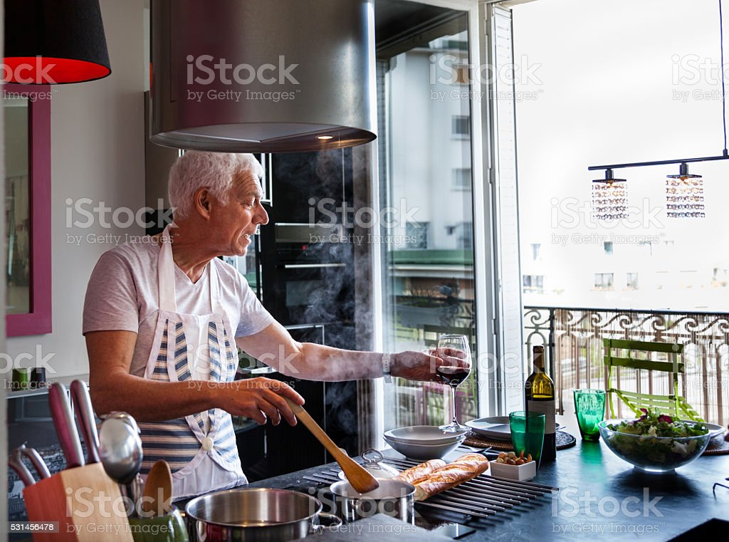senior Italian man cooks meal drinks wine  stylish modern apartment stock photo