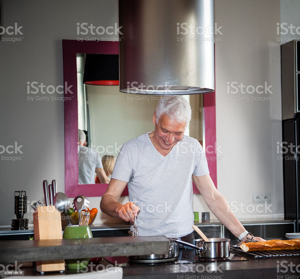 senior Italian man cooks meal in stylish modern apartment stock photo
