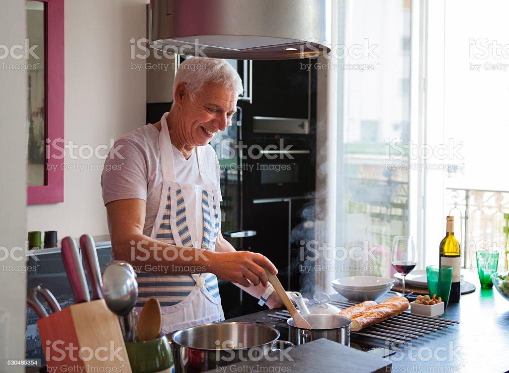 senior Italian man cooks meal in stylish modern apartment stock photo